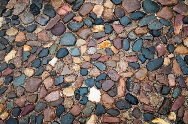 Belle surface abstraite naturelle texturée pour les arrière-plans pavés avec pierres rondes