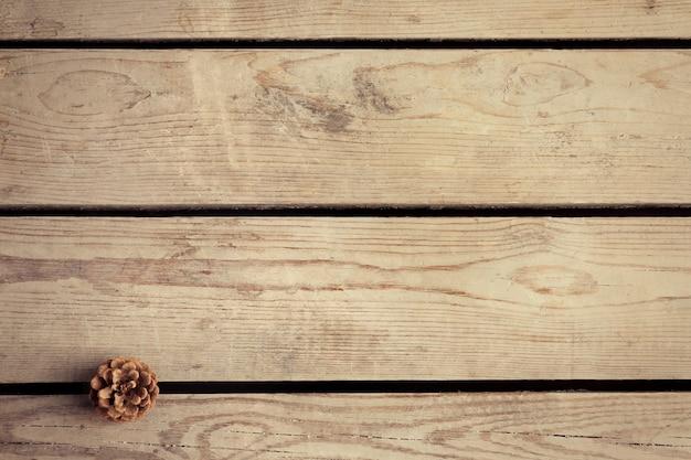 Belle surface d'hiver simple avec pomme de pin sur la texture en bois