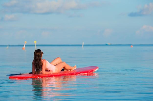 Belle surfeuse femme surfant dans la mer turquoise