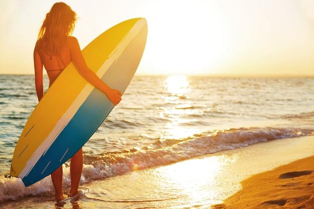 Belle surfeuse sur la plage de sable au coucher du soleil