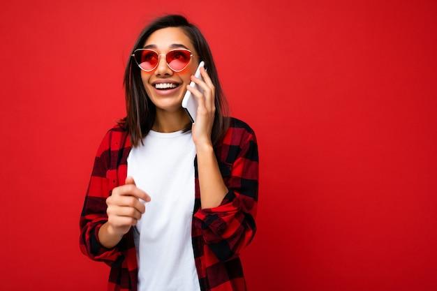 Belle surprise heureuse jeune femme brune portant un t-shirt blanc élégant en chemise rouge et des lunettes de soleil rouges isolées sur fond rouge, parlant au téléphone portable en regardant la caméra.