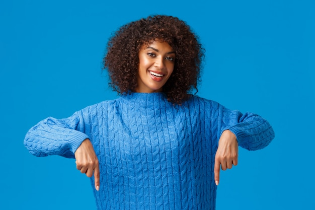 Belle et sympathique jeune femme afro-américaine sensuelle en pull d'hiver, pointant vers le bas, invitant les sourcils à travers un site web génial, faisant des achats en ligne, indiquant la publicité du bas, mur bleu