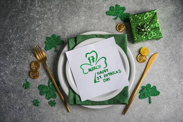 Belle table de fête pour la saint-patrick avec des couverts et des symboles chanceux. copiez le spase au centre. mise à plat.