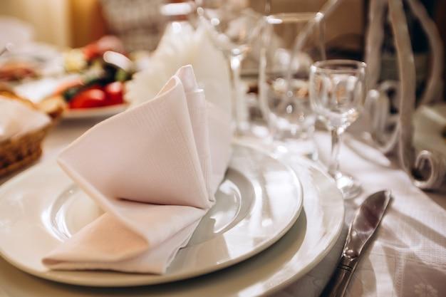 Belle table de mariage élégante décorée pour le dîner avec des bouquets de fleurs blanches, des chandeliers et une nappe blanche et des assiettes en porcelaine