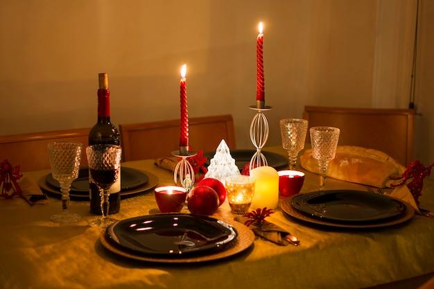 Belle table préparée et prête pour le dîner de noël avec la lumière chaleureuse des bougies.