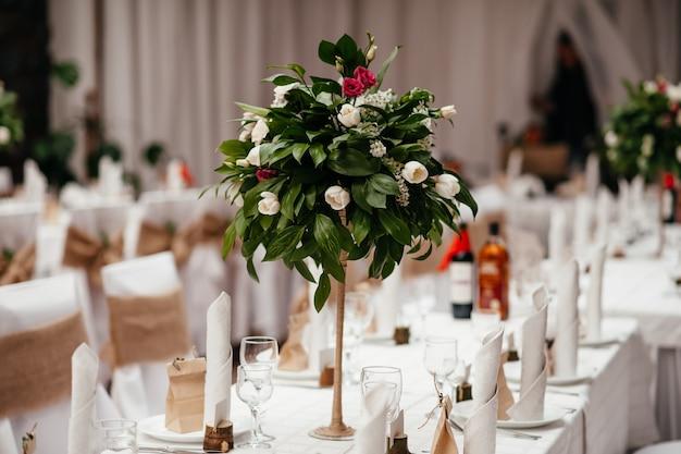 Belle table ronde servie avec des décorations dans la salle à manger. petit lapin jaune, branches de saule décorées de couleurs