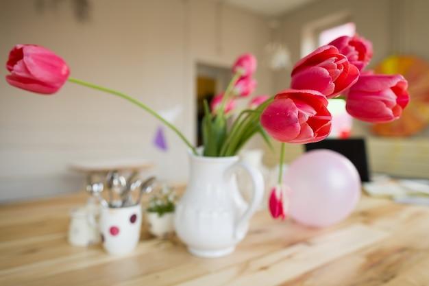 Belle table avec des tulipes rouges, ne m'oubliez pas et des tasses sur la table en bois.