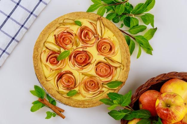Belle tarte aux pommes maison sur fond blanc avec des pommes fraîches. vue de dessus.