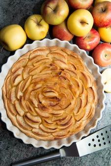 Belle tarte aux pommes avec des pommes rouges et jaunes