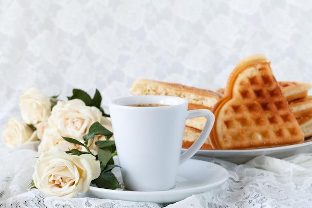 Belle tasse blanche de café noir et fleur rose sur fond blanc