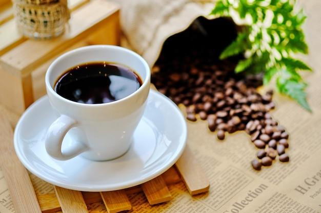 Belle tasse à café blanche sur les arbres à feuilles de table arrière-plan flou.
