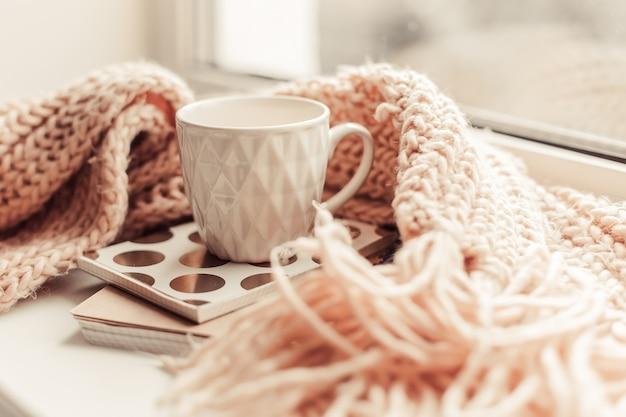 Belle tasse de thé rose avec carnet et écharpe tricotée