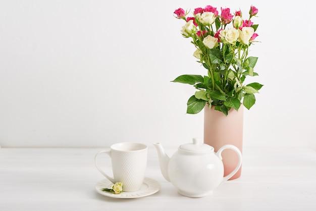 Belle tasse et théière sertie de fleurs roses