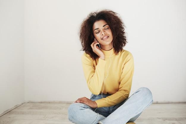 Belle tendre femme africaine souriante, les yeux fermés, écouter de la musique dans les écouteurs en appréciant.