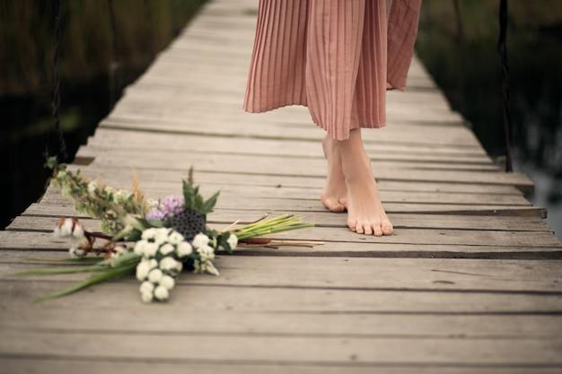 Belle tendre fille vêtue d'une robe couleur pêche marchant sur un pont en bois rural avec un bouquet de fleurs
