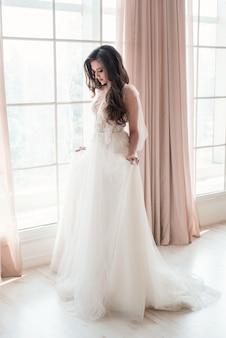 Belle et tendre jeune mariée vêtue d'une robe de mariée en séance photo de mariage photostudio