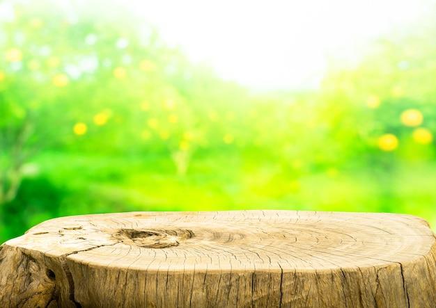 Belle texture de la vieille table de souche d'arbre sur fond de ferme de jardin de fruits flou.pour créer un affichage de produit ou une disposition visuelle clé de conception.