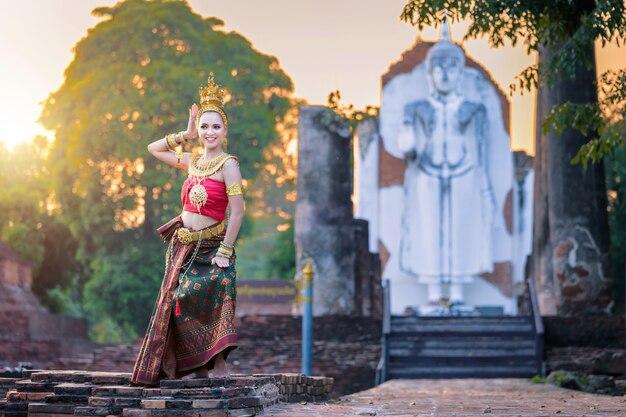 Belle thaïlandaise jeune femme en costume traditionnel avec fond de temple de style thaïlandais.