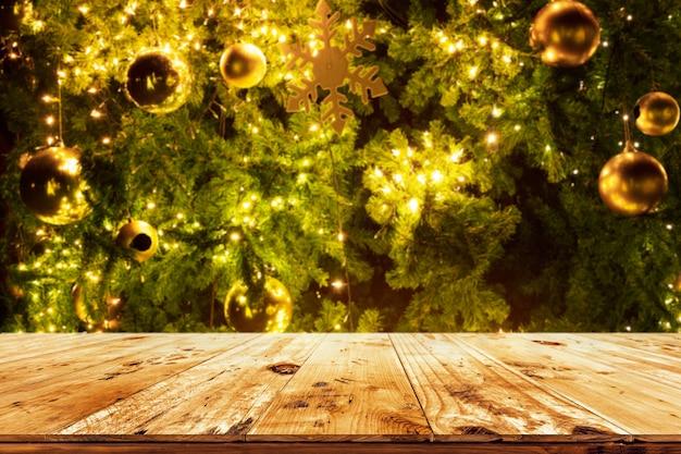 Belle toile de fond d'arbre de noël et lumières avec haut de table en bois vide. prêt pour l'affichage ou le montage de votre produit