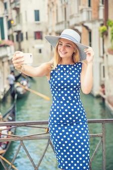 Belle touriste voyageuse en robe à pois bleus fait un selfie à venise en italie. jolie blonde mannequin jeune femme.