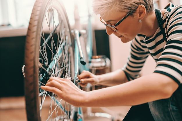 Belle travailleuse de race blanche avec des cheveux blonds courts et des lunettes accroupies et réparant le vélo. intérieur de l'atelier de vélo.