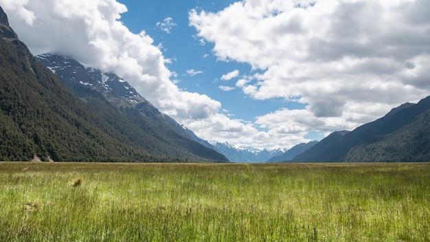 Belle vallée pittoresque entourée de montagnes avec des champs verts en premier plan et un ciel bleu