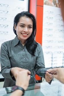 Une belle vendeuse donne une paire de lunettes à un client lorsqu'elle essaie chez un opticien