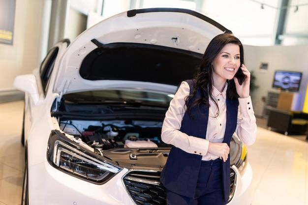 Belle vendeuse inspecter une voiture neuve et parle par téléphone dans la salle d'exposition du concessionnaire