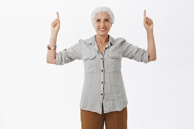 Belle vieille dame souriante pointant les doigts vers le haut, montrant la publicité