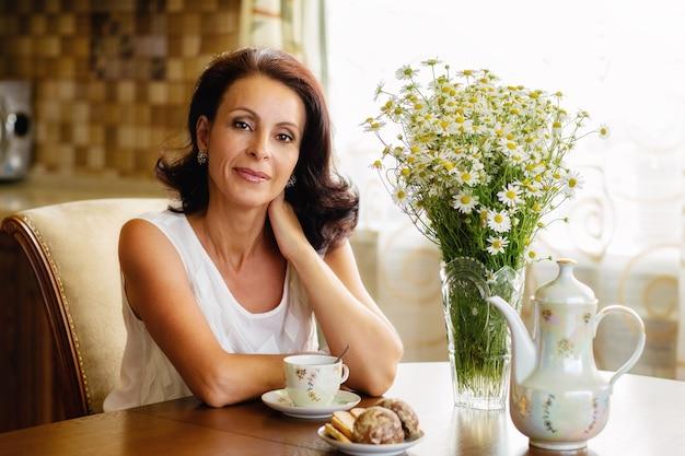 Belle vieille femme dans un chemisier blanc assis à une table ronde avec un bouquet de marguerites, souriant et buvant du café avec des biscuits dans la cuisine.