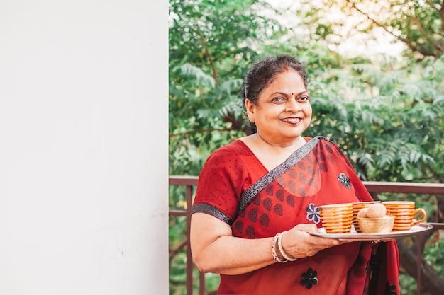 Belle vieille femme indienne dans un sari tenant un plateau avec des tasses à thé