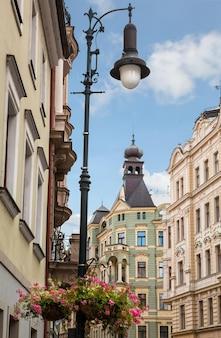 Une belle vieille lampe murale sur une rue historique près du château de prague, avec des toits et des fenêtres du quartier hradcany