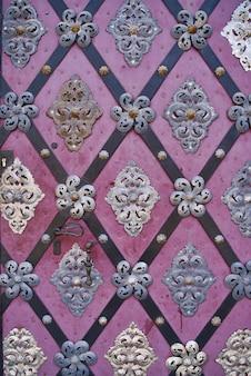 Belle vieille porte en bois vieilli avec des ornements métalliques