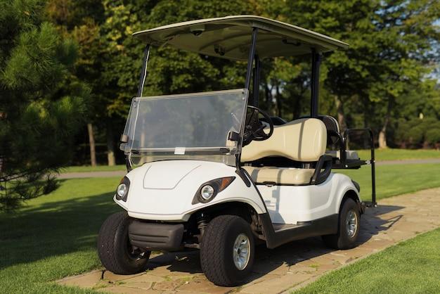 Belle voiture de golf blanche de luxe avec voiturette du club de golf.