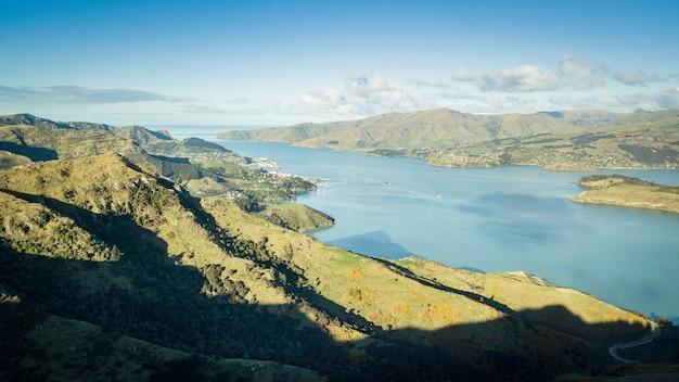 Belle vue aérienne sur la baie entourée de collines verdoyantes governors bay nouvelle-zélande