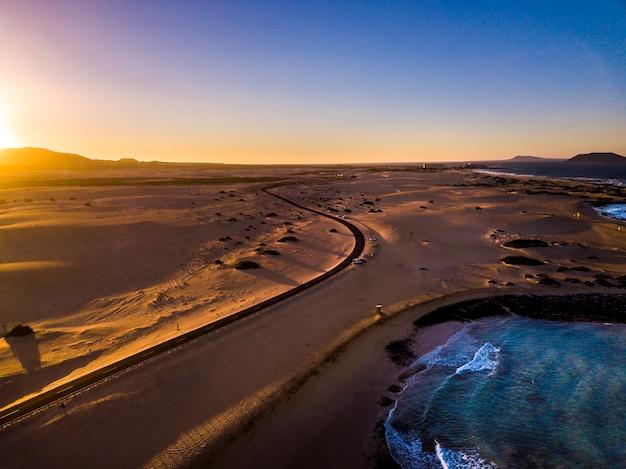 Belle vue aérienne de la plage de la côte pendant le coucher du soleil - océan bleu et sable jaune et désert avec la lumière du soleil viennent des montagnes