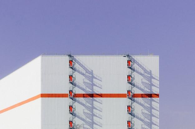 Belle vue sur un bâtiment blanc traversé d'une ligne orange et d'un escalier menant au toit