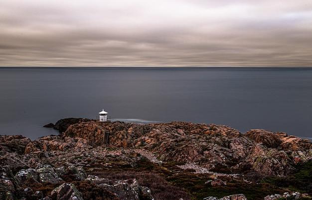 Belle vue sur un bord de mer rocheux par une journée sombre