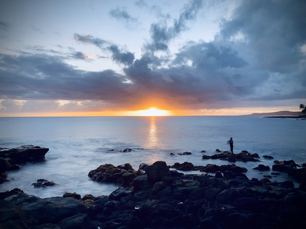 Belle vue sur le coucher du soleil dans le ciel nuageux sur l'océan calme par la côte rocheuse
