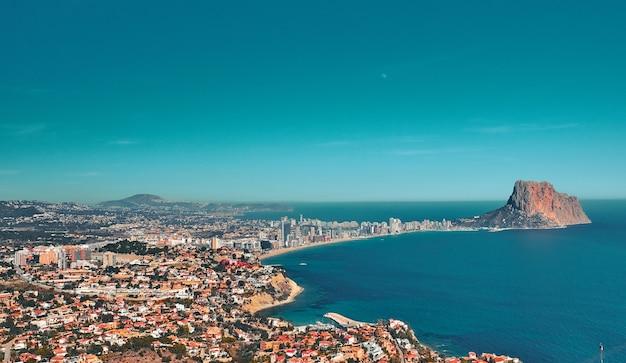 Une belle vue depuis une falaise sur une ville côtière au bord de la mer avec de nombreux petits bâtiments par temps ensoleillé.