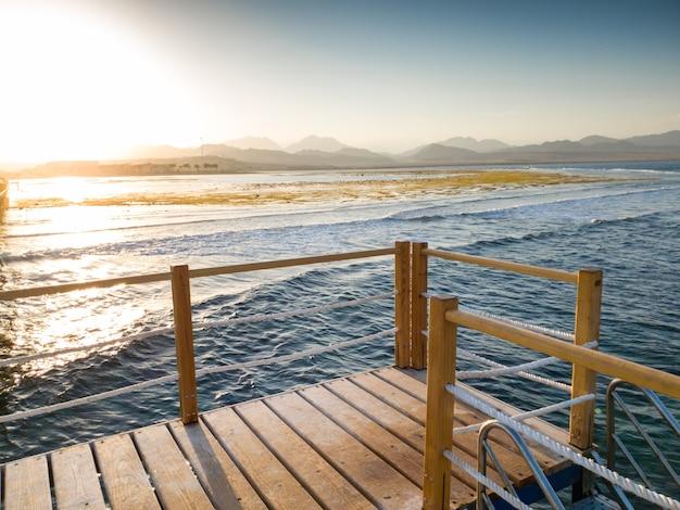 Belle vue depuis la jetée ou le pont en bois sur les vagues calmes de l'océan et le coucher de soleil sur les montagnes