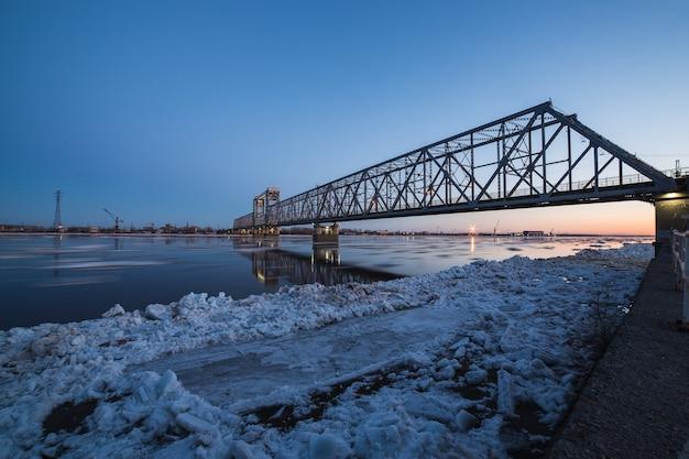 Belle vue sur la dérive de glace sous le pont ferroviaire à arkhangelsk, russie. beau mouvement de glace sur le nord de la rivière dvina, paysage du soir.