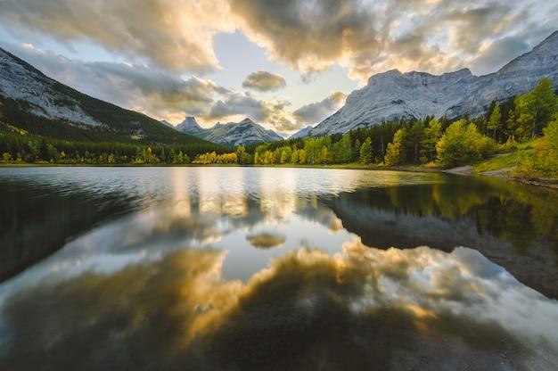Belle vue sur un étang reflétant les arbres verts sur la rive entourée de montagnes enneigées