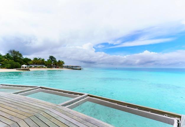 Belle vue sur l'île tropicale des maldives, nuages blancs, ciel bleu et mer turquoise cristalline
