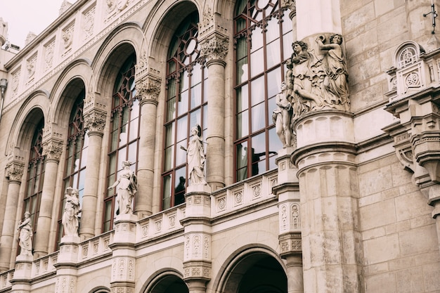 Belle vue sur un immeuble avec des statues sur la façade et de hautes fenêtres voûtées à budapest