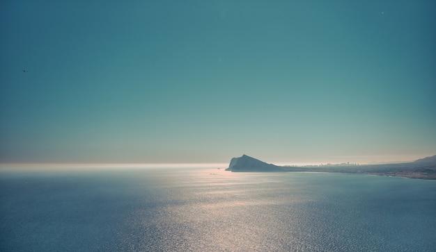 Belle vue mer panoramique avec une petite île, temps brumeux.