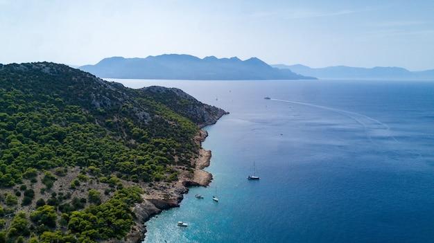 Belle vue sur la péninsule verte avec yachts et bateaux à proximité en grèce