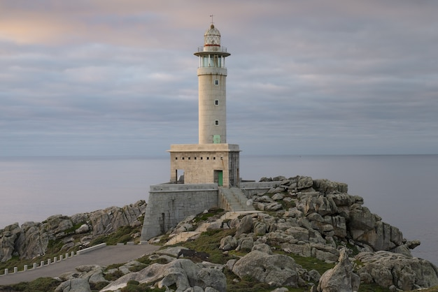 Belle vue sur un phare de punta nariga sur une falaise côtière au lever du soleil en galice, espagne