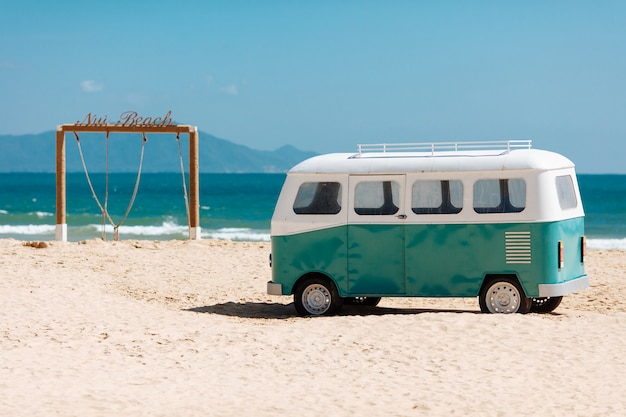 Belle vue sur la plage avec arche en bois et bus hippie