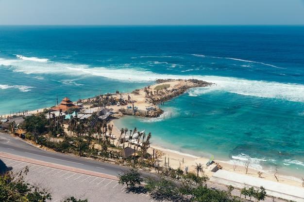 Belle vue sur la plage de melasti. mer bleue avec vagues, ciel clair et sable blanc.